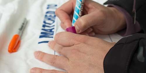 A resident writes their specialty and location in bright magic marker on a t-shirt.